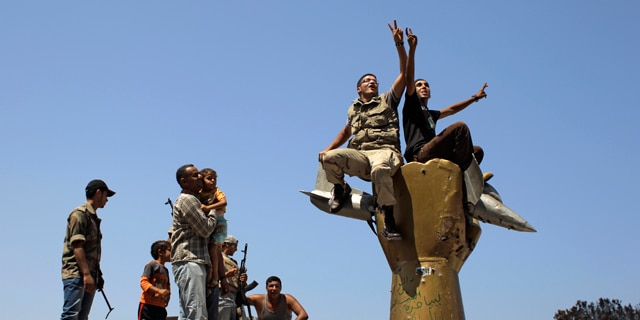 Aug. 24: Rebel fighters celebrate as they stand on top of the monument inside Qaddafi's compound in Bab Al-Aziziya in Tripoli, Libya.