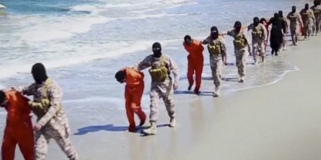 Islamic State militants lead what are said to be Ethiopian Christians along a beach in Wilayat Barqa, in this still image from an undated video made available on a social media website on April 19, 2015. REUTERS/Social Media Website via Reuters