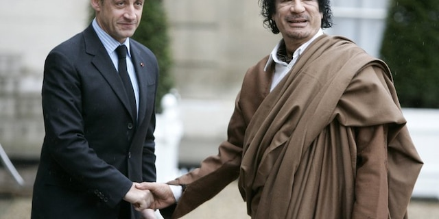 French President Nicolas Sarkozy, left, greets Libyan leader Col. Moammar Gadhafi upon his arrival at the Elysee Palace, in Paris, Dec. 10, 2007.