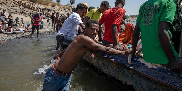 Tigray refugees who fled the conflict in the Ethiopia's Tigray ride a boat on the banks of the Tekeze River on the Sudan-Ethiopia border, in Hamdayet, eastern Sudanon Saturday. The U.N. refugee agency says Ethiopia's growing conflict has resulted in thousands fleeing from the Tigray region into Sudan as fighting spilled beyond Ethiopia's borders and threatened to inflame the Horn of Africa region. (AP Photo/Nariman El-Mofty)