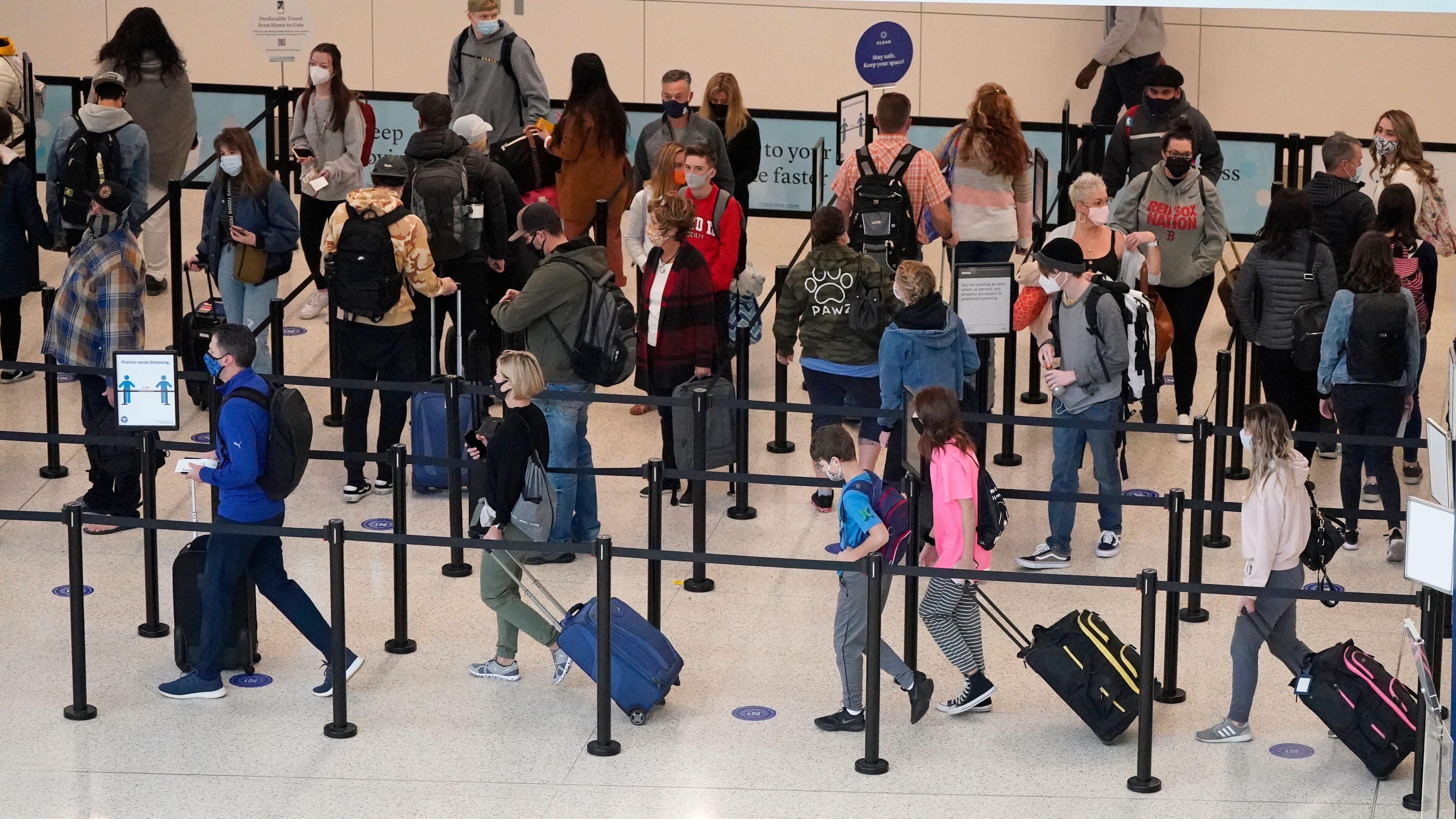 Air travelers line up to go through a security checkpoint at Salt Lake City International Airport Wednesday, Nov. 25, 2020, i