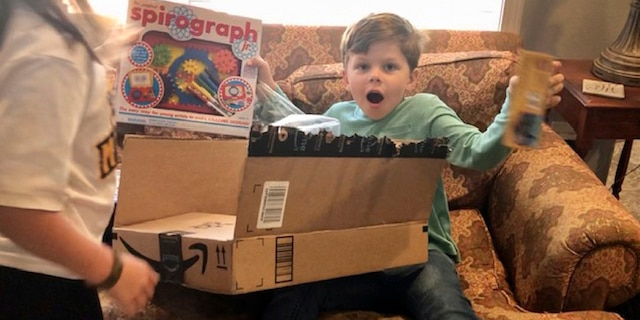 Chip Matthews, 6, opens a birthday present at his home in Opelika, Ala., on Thursday, Nov. 5, 2020. Matthews was given an extra birthday surprise when postal worker, Tawanna Purter, gave him $2 as a gift. (Bonnie Matthews via AP)