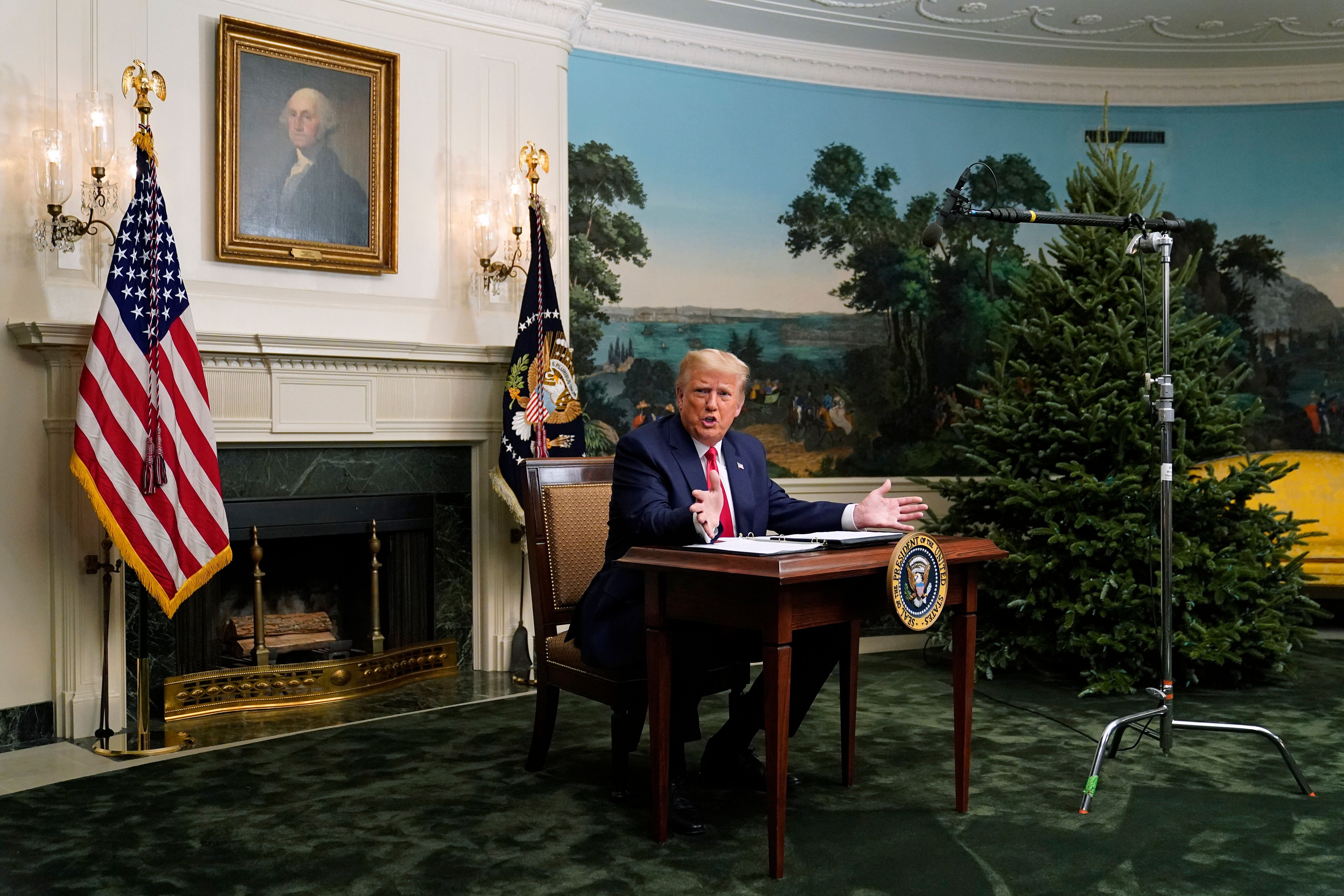 President Donald Trump spoke with reporters following a video chat with members of the military and the tiny desk he sat at b