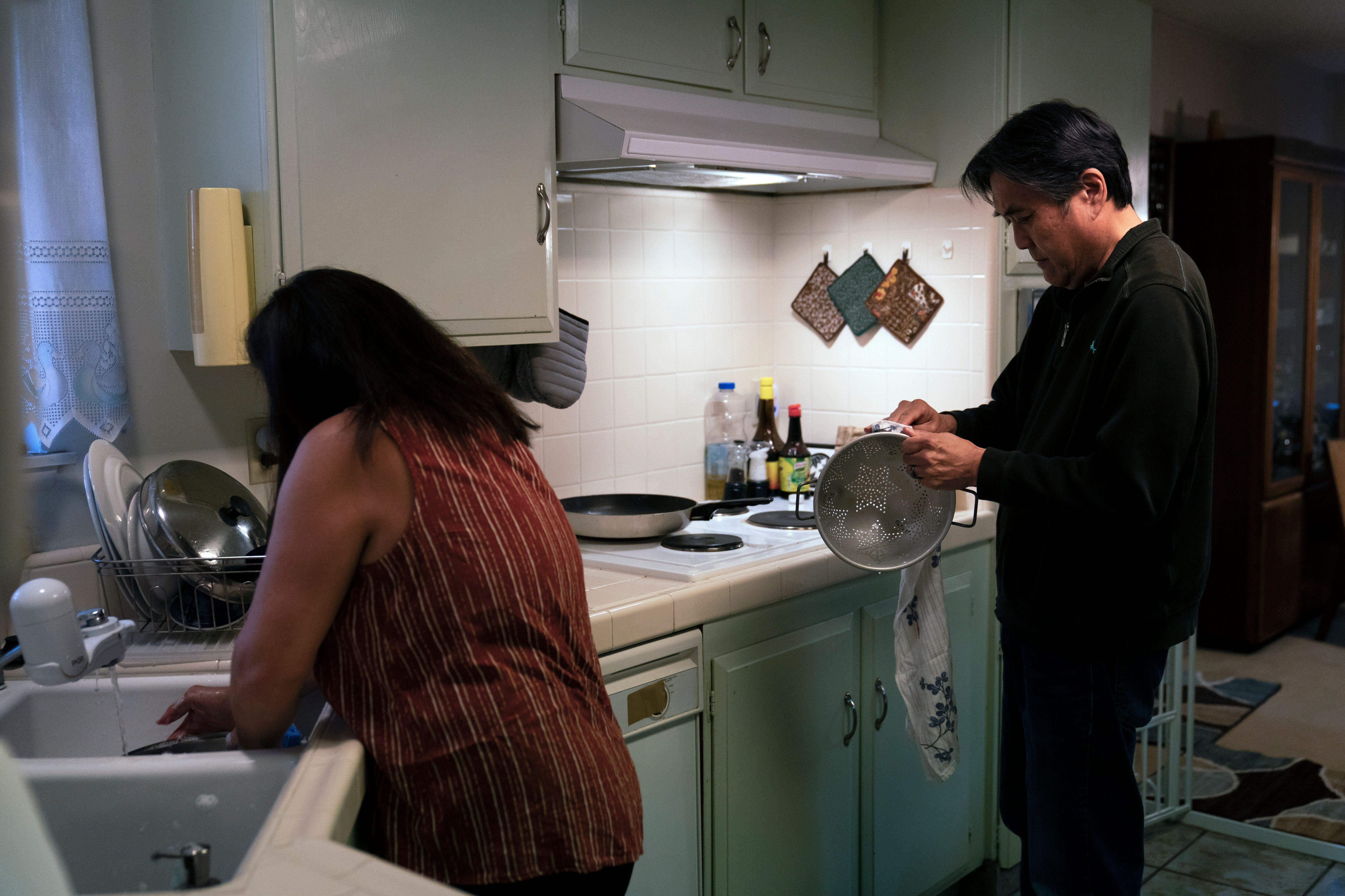 Kerry Osaki, right, helps his wife, Lena Adame, in the kitchen in Fountain Valley, Calif., on Nov. 25, 2020. For years, Osaki