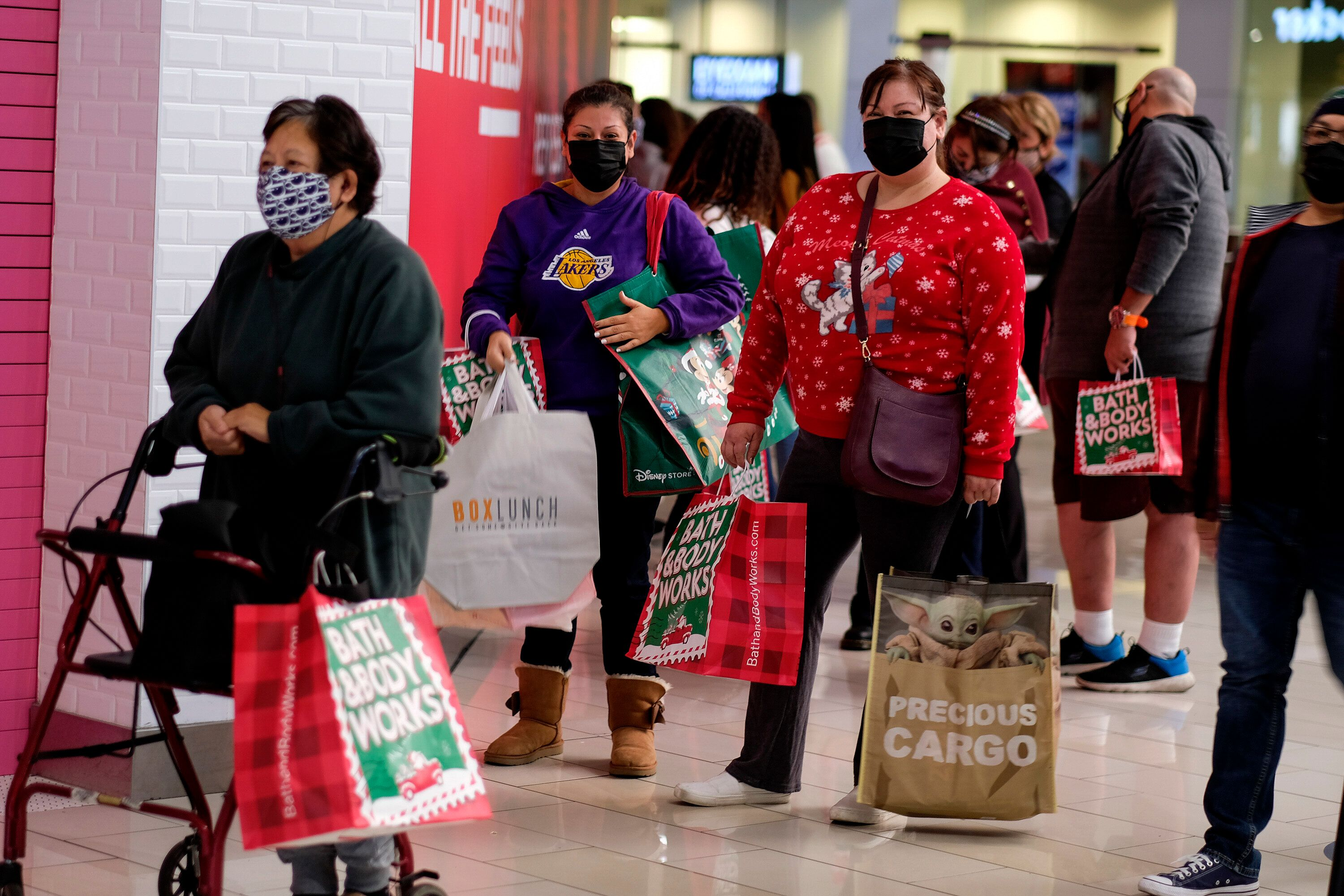Black Friday shoppers wearing face masks wait in line to enter a store at the Glendale Galleria in Glendale, Calif., Friday,