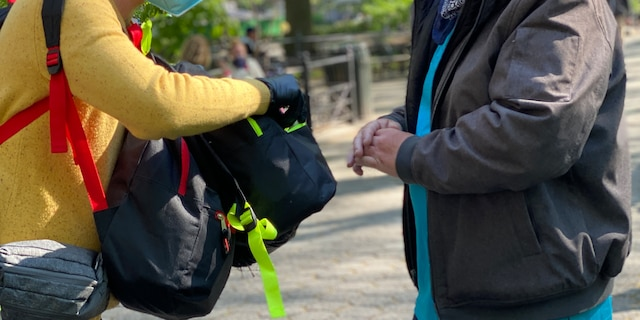 Jayson Conner hands someone a backpack. Conner himself experienced homelessness in the early 2000s. (Courtesy of Backpacks for the Street)