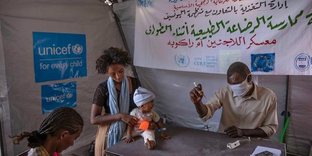 Tigray women who fled the conflict in Ethiopia's Tigray region, take shelter inside a UNICEF tent, as Filippo Grandi, U.N. High Commissioner for Refugees, visits Umm Rakouba refugee camp in Qadarif, eastern Sudan, Saturday, Nov. 28, 2020. (AP Photo/Nariman El-Mofty)