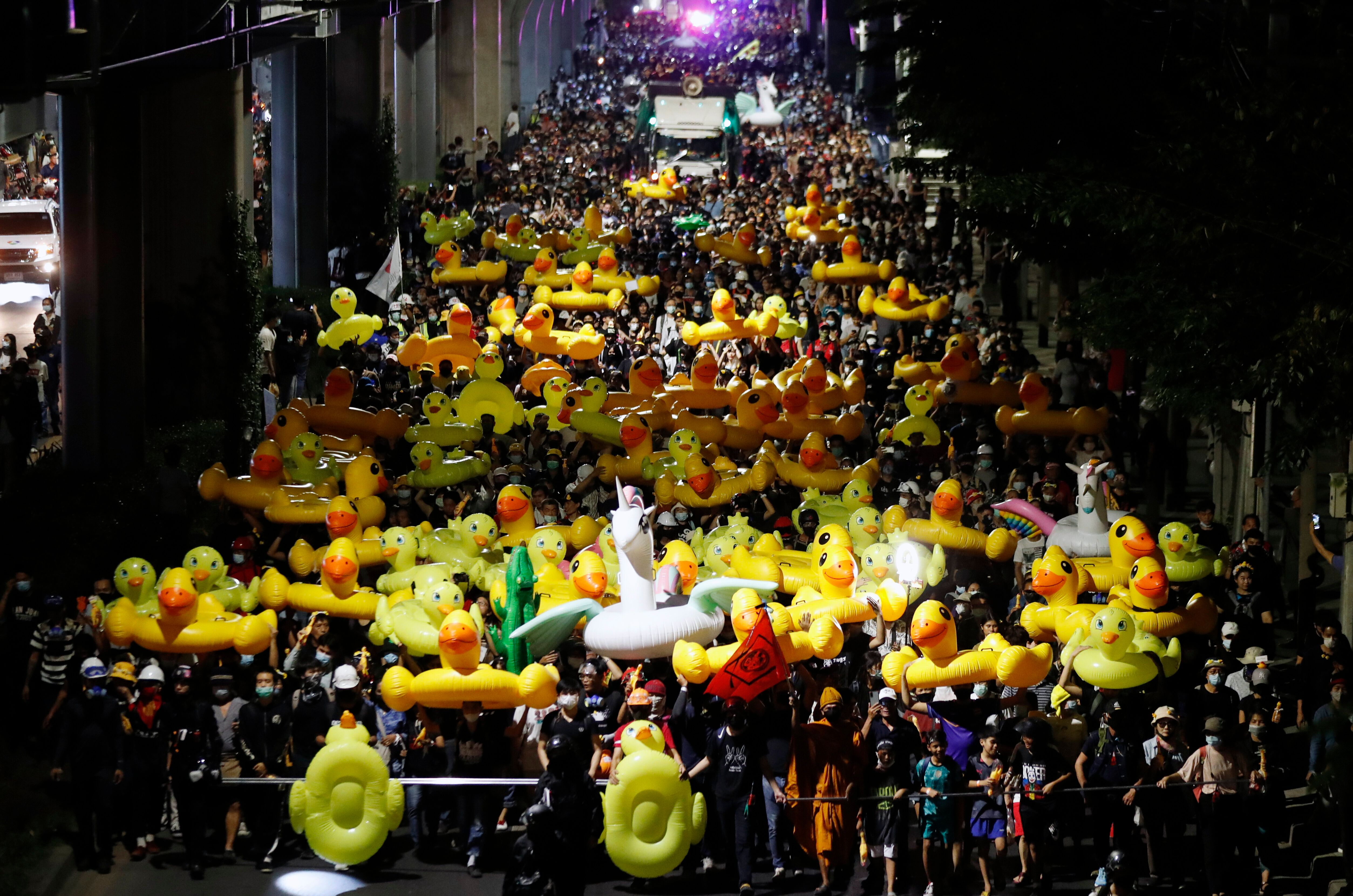 Protesters carry inflatable yellow ducks, which have become good-humored symbols of resistance during anti-government rallies