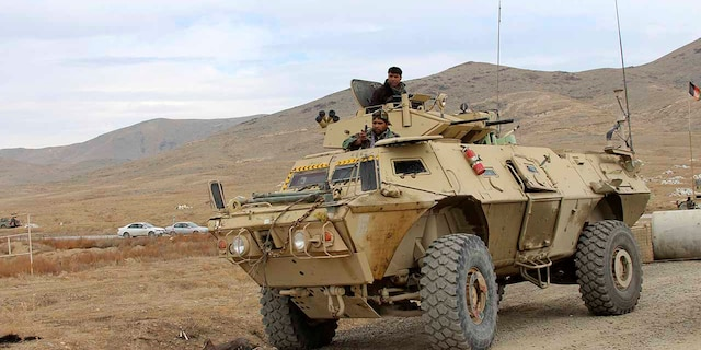 Afghan national army soldiers arrive at the site of a suicide bombing in Ghazni province west of Kabul, Afghanistan, Sunday, Nov. 29, 2020. Over 30 people were killed on Sunday in two separate suicide bombings in Afghanistan that targeted a military base and a provincial chief, officials said. (AP Photo/Rahmatullah Nikzad)