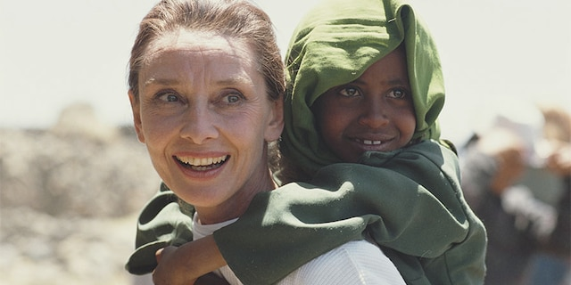 Actress and humanitarian Audrey Hepburn (1929 - 1993) carrying an Ethiopian girl on her back while on her first field mission for UNICEF in Ethiopia, 16th-17th March 1988.