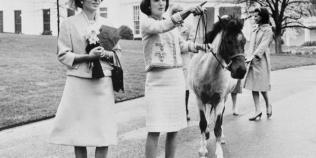 In this April 12, 1962, file photo first lady Jacqueline Kennedy gives a guided tour of the White House grounds to Empress Farah Pahlavi of Iran in Washington. Kennedy leads her daughter Caroline's pony, Macaroni, which had been nuzzling the empress, attracted by the daffodils she was carrying. (AP Photo/Pool)