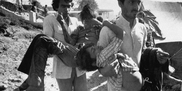 In this Dec. 5, 1984, file photo, two men carry to a hospital children blinded by the Union Carbide chemical pesticide leak in Bhopal, India. (AP Photo/Sondeep Shankar, File)