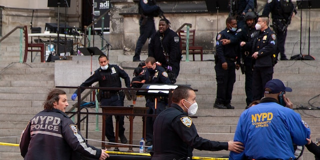 New York police officers carry a suspected gunman in a stretcher down the steps of Cathedral Church of St. John the Divine, Sunday, Dec. 13, 2020, in New York. (AP Photo/Ted Shaffrey)