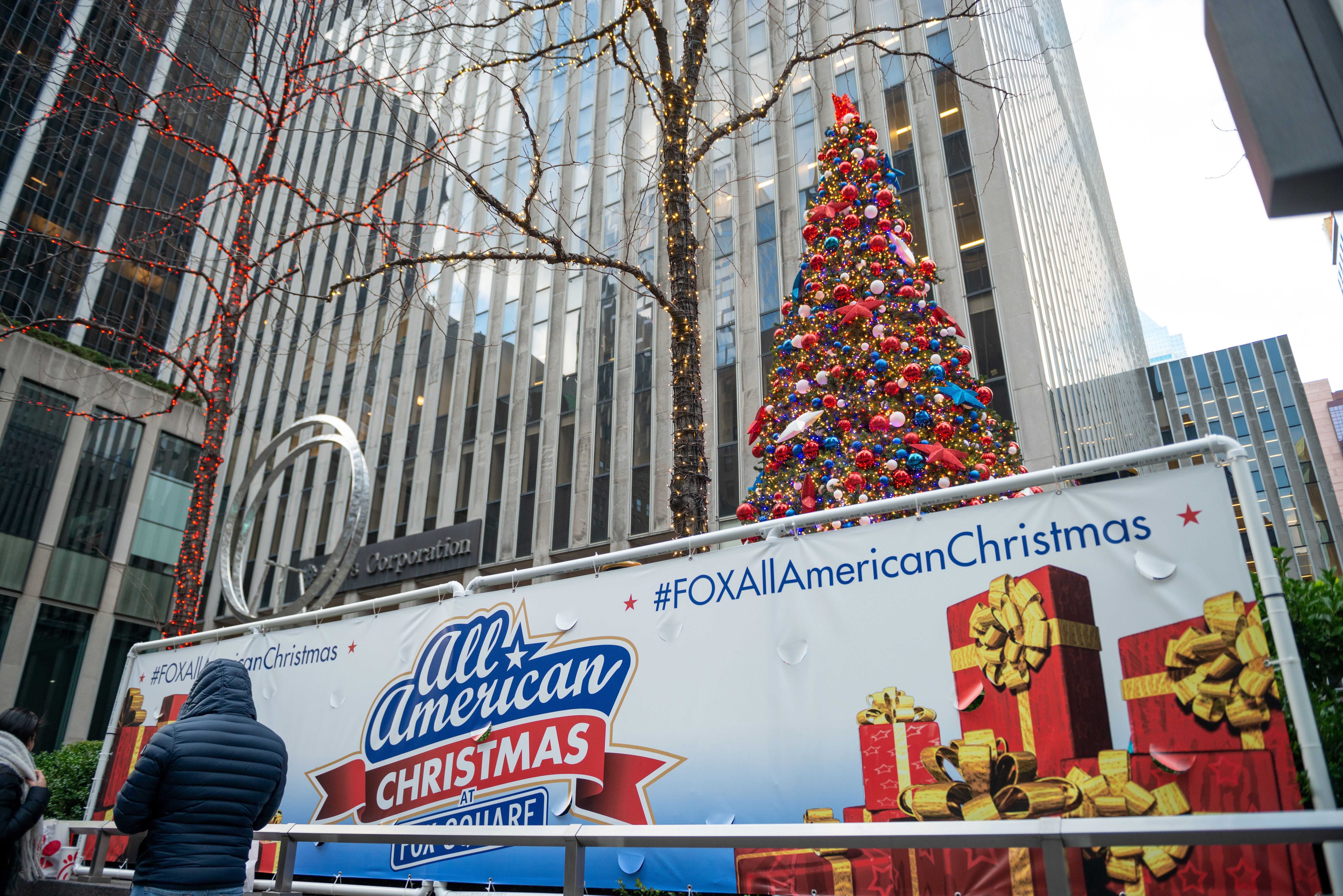 """An """"All American Christmas at Fox Square"""" sign near Christmas decorations in front of the News Corporation building in New Yo"""