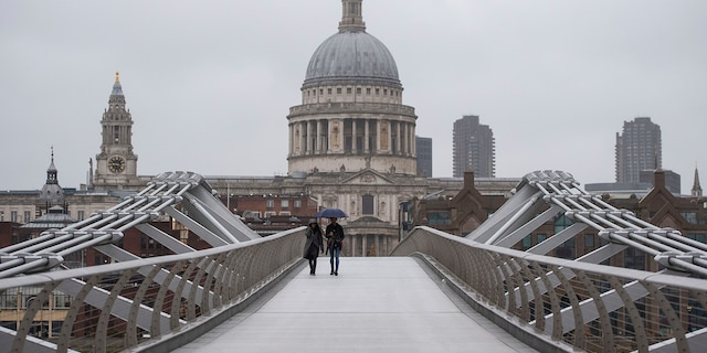People walk across the Millennium Bridge in London, Monday, Dec. 21, 2020. Millions of people in England have learned they must cancel their Christmas get-togethers and holiday shopping trips. (Dominic Lipinski/PA via AP)
