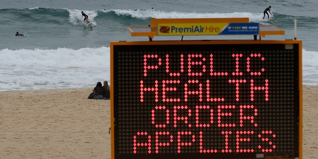 Surfers ride a wave past a sign at a beach in Sydney, Australia, Saturday, Dec. 19, 2020. Sydney's northern beaches will enter a lockdown similar to the one imposed during the start of the COVID-19 pandemic in March as a cluster of cases in the area increased to more than 40. (AP Photo/Mark Baker)