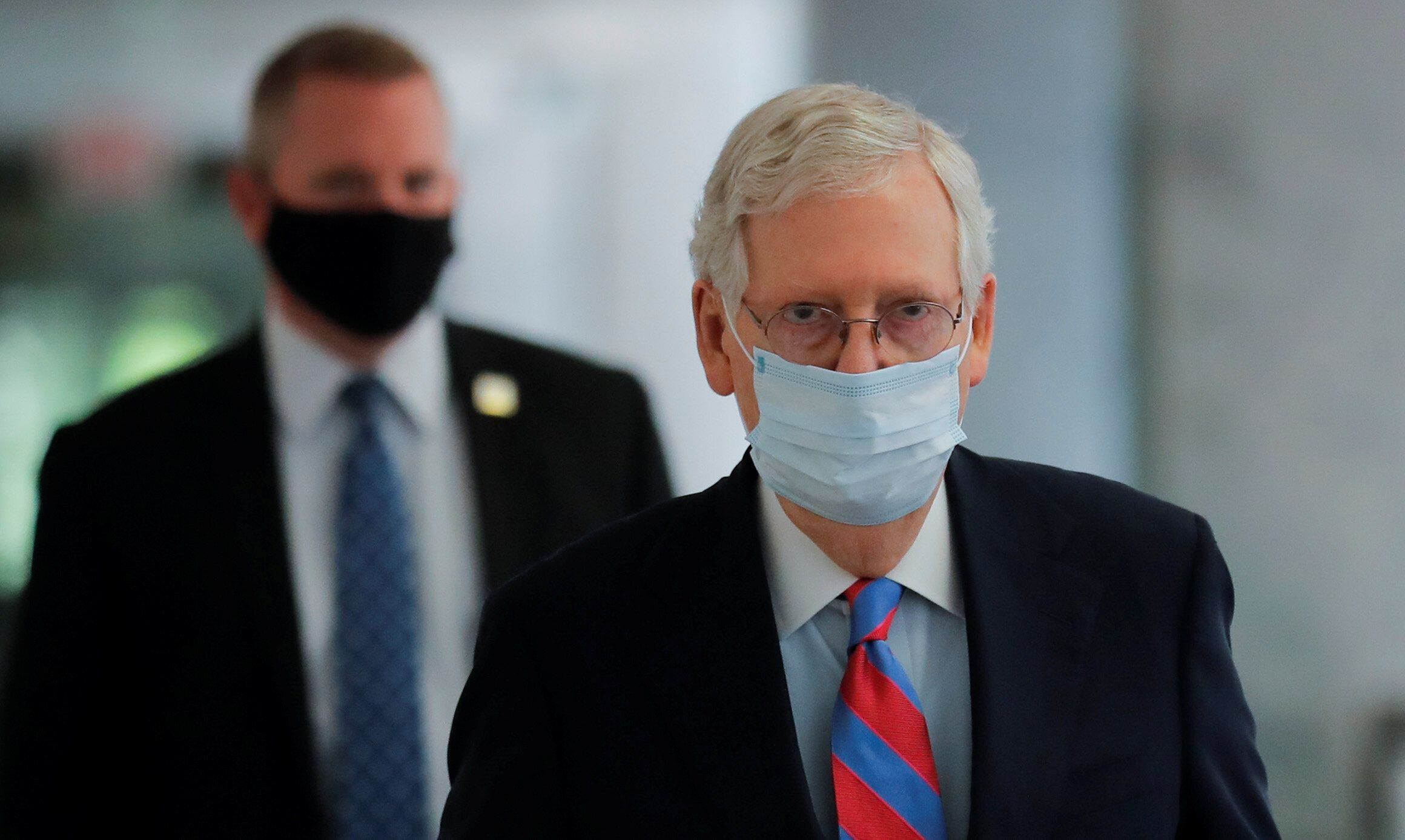 Senate Majority Leader Mitch McConnell (R-Ky.) wears a protective face mask as he walks down a hallway of the Hart Senate Off