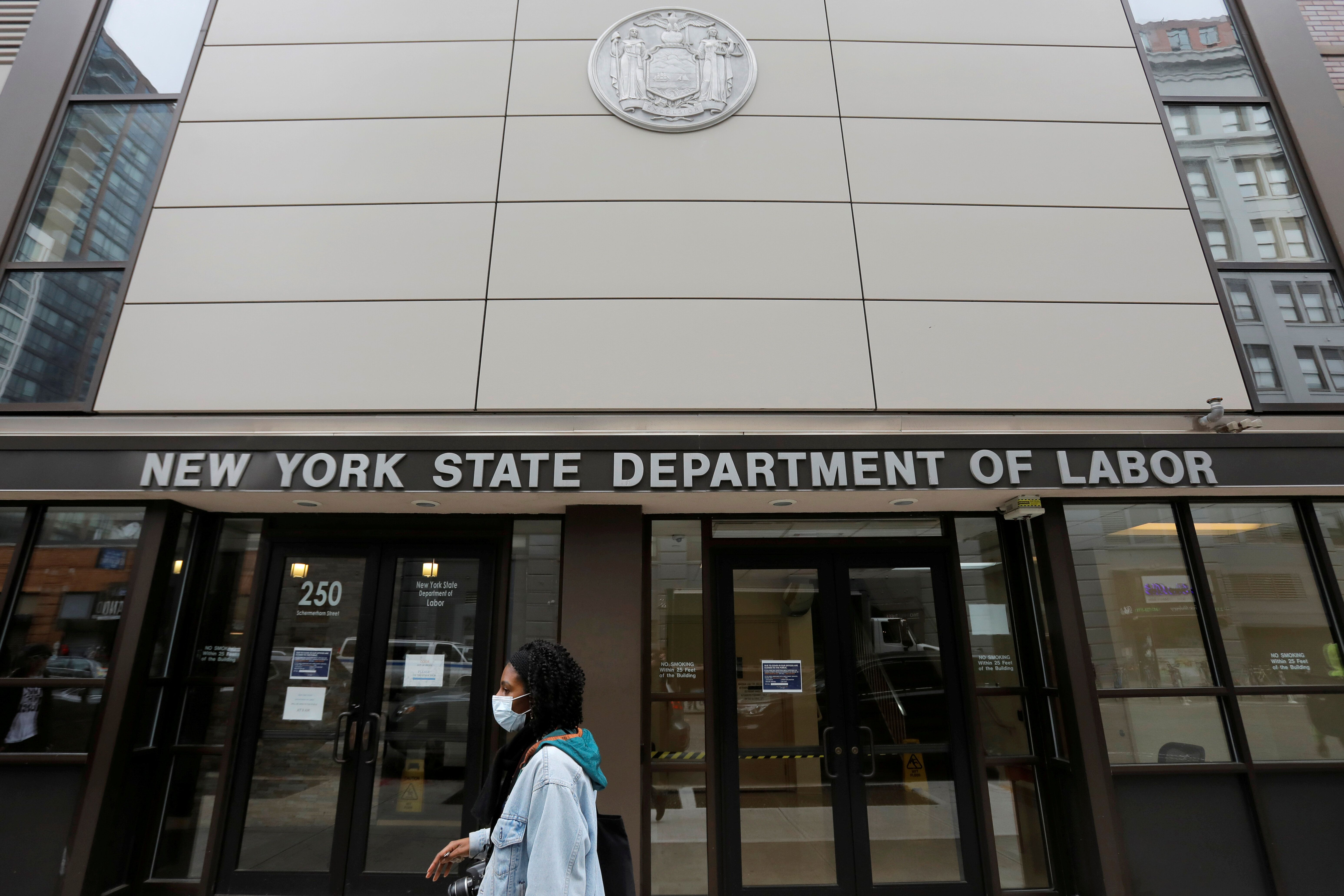 A person walks by the entrance of the New York State Department of Labor offices, which closed to the public due to the coron