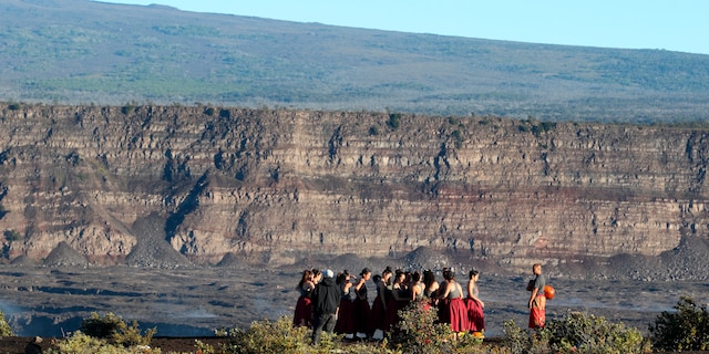 FILE - In this April 25, 2019, photo, a group of Native Hawaiians stand next to the collapsed caldera floor of Kilauea volcano in Hawaii Volcanoes National Park on the Big Island. The U.S. Geological Survey says the Kilauea volcano on Hawaii's Big Island has erupted. The eruption began late Sunday, Dec. 20, 2020 within the Halema'uma'u crater. The volcano is located within Hawaii Volcanoes National Park. (AP Photo/Caleb Jones, File)