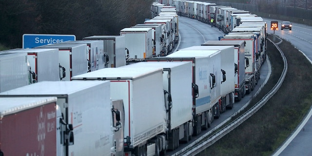 Trucks are parked along the M20 motorway where freight traffic is halted whilst the Port of Dover remains closed, in Ashford, Kent, England, Tuesday, Dec. 22, 2020. Trucks waiting to get out of Britain backed up for miles and people were left stranded at airports as dozens of countries around the world slapped tough travel restrictions on the U.K. because of a new and seemingly more contagious strain of the coronavirus in England. (Andrew Matthews/PA via AP)