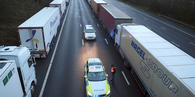 Police patrol along the M20 motorway where freight traffic is halted whilst the Port of Dover remains closed, in Ashford, Kent, England, Tuesday, Dec. 22, 2020. (Andrew Matthews/PA via AP)