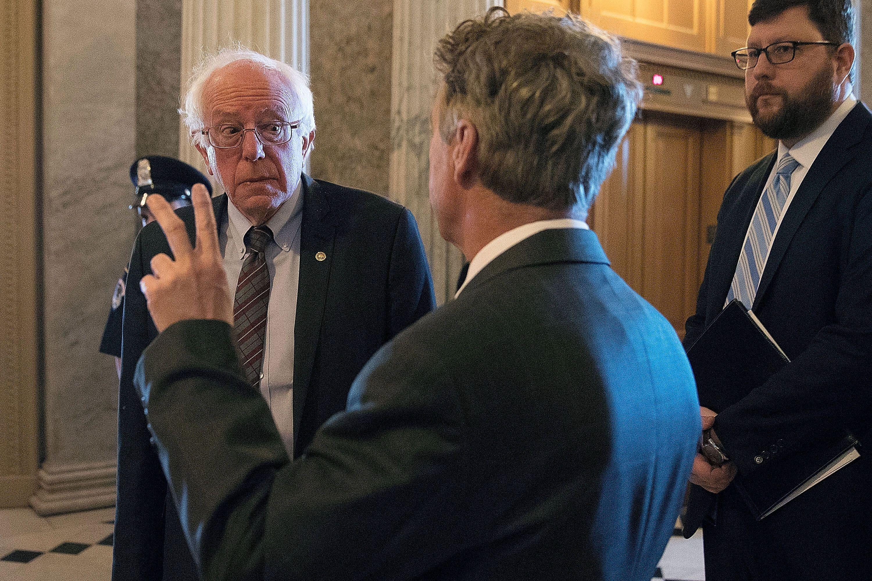 Sen. Bernie Sanders (I-Vt.), left, talks with Sen. Rand Paul (R-Ky.) in April 2018. Paul has called for pardoning Snowden, wh