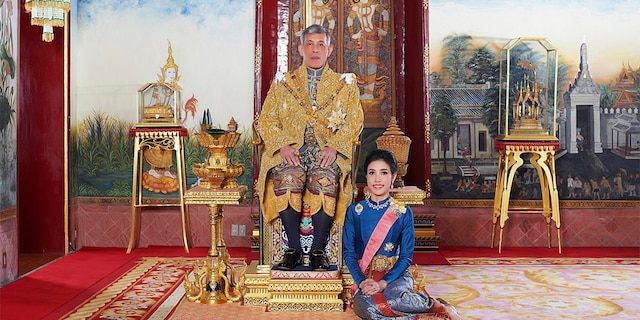 In this undated photo posted in 2019, on the Thailand Royal Office website, Thailand's King Maha Vajiralongkorn sits on the throne with his official consort Sineenatra Wongvajirabhakdi at the royal palace. (Thailand Royal Office via AP)