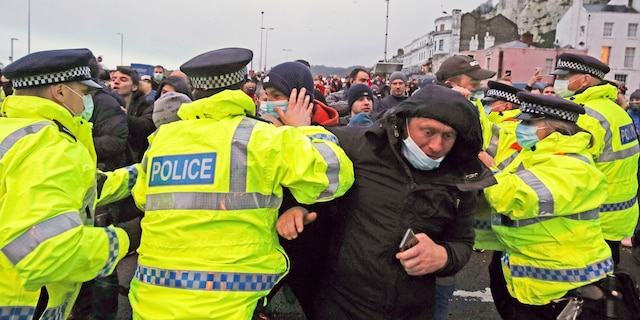 Truck drivers argue with police holding them back at the entrance to the Port of Dover, in Kent, England, Wednesday Dec. 23, 2020. (Steve Parsons/PA via AP)