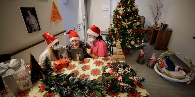 """Caterina Bertocchi is flanked by health care worker Michela Valle, right, and director Maria Giulia Madaschi as she talks a video call with Irene Schiavone, a donor unrelated to her, who bought and sent her a Christmas present through an organization dubbed """"Santa's Grandchildren,"""" at the Martino Zanchi nursing home in Alzano Lombardo, one of the areas that most suffered in the first wave of COVID-19, in northern Italy, Saturday, Dec. 19, 2020. (AP Photo/Luca Bruno)"""