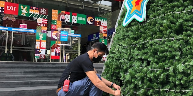A worker wearing a face mask to help prevent the spread of coronavirus prepares an artificial Christmas tree outside a shopping mall that would normally be busy with foreign tourists in Bangkok on Wednesday, Dec. 23, 2020. Thailand has kept the coronavirus largely in check for most of the year but is facing a challenge from a large outbreak that threatens to undo months of efforts to contain the virus and hasten recovery of an ailing economy that relies heavily on tourism.(AP Photo/Adam Schreck)