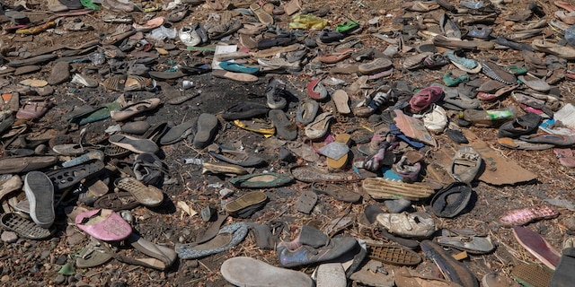 Shoes left behind belonging to Tigrayan refugees are scattered near the banks of the Tekeze River on the Sudan-Ethiopia border after Ethiopian forces blocked people from crossing into Sudan, in Hamdayet, eastern Sudan, Tuesday, Dec. 15, 2020. (AP Photo/Nariman El-Mofty)