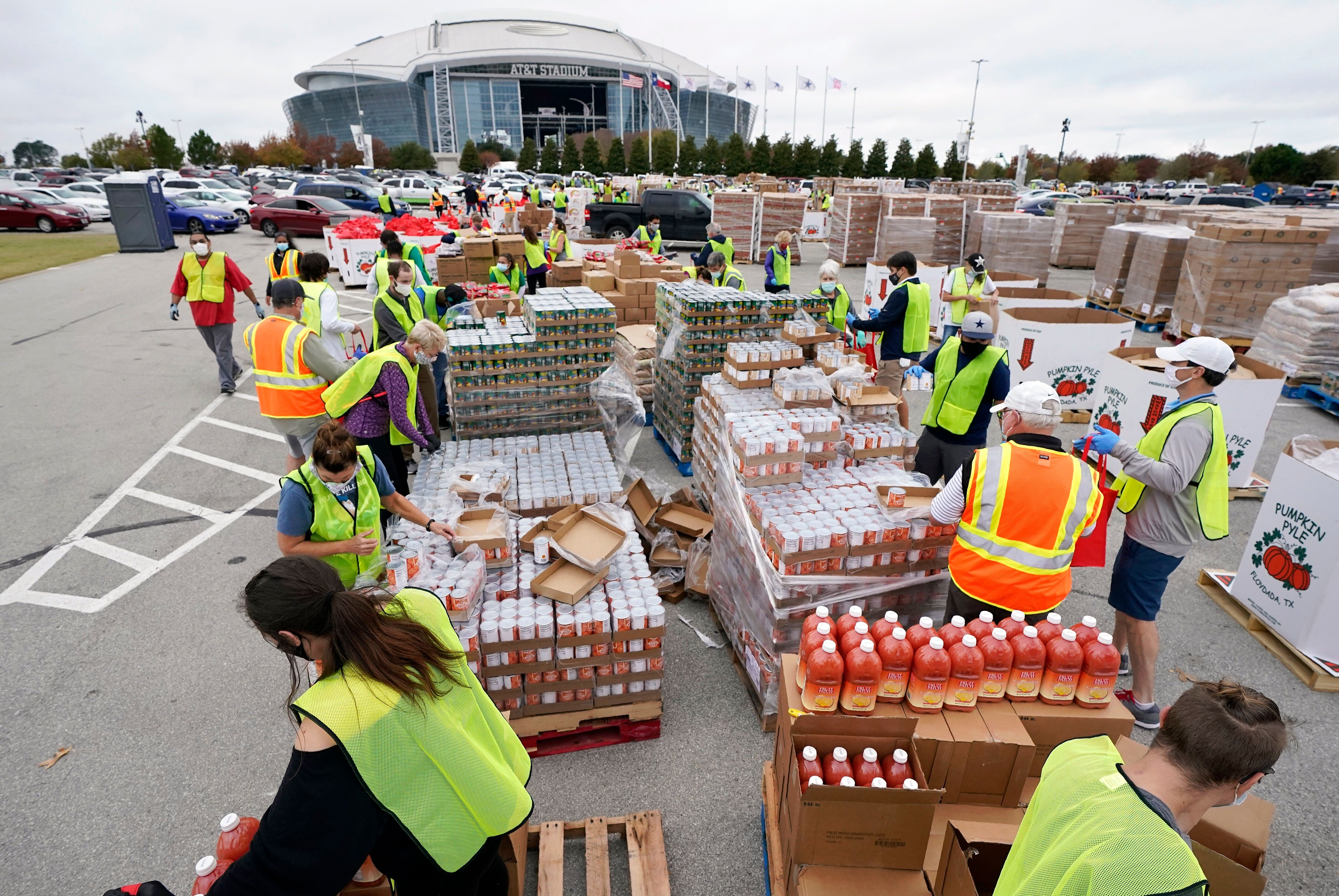 Volunteers build bags of dry goods in a parking lot outside of AT&T Stadium during a Tarrant Area Food Bank mobile pantry dis