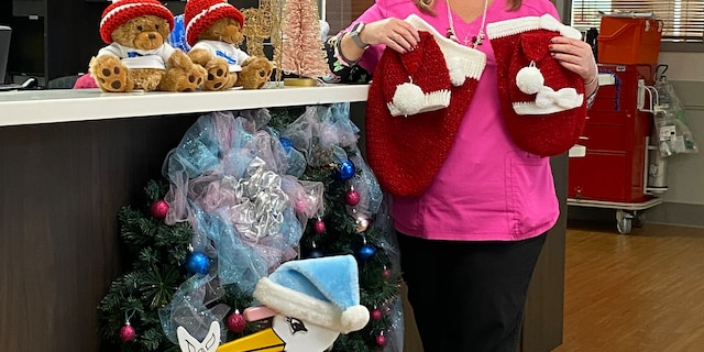Nurse Lori Shaffer holding up some of the Christmas outfits that she and Pat Vicino made for newborn babies at St. Lucie Medical Center in Port St. Lucie, Florida.
