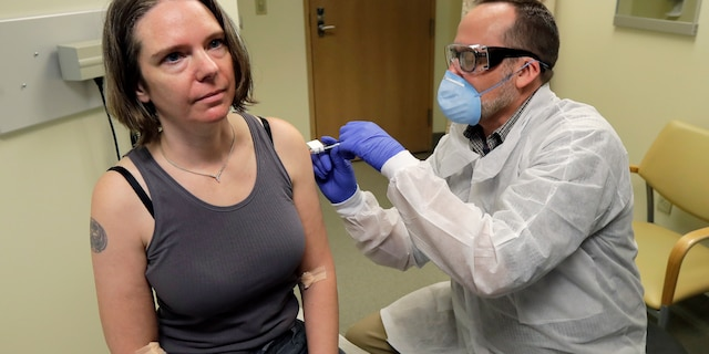 In this March 16, 2020, file photo, a pharmacist gives Jennifer Haller, left, the first shot in the first-stage safety study clinical trial of a potential vaccine for COVID-19 at the Kaiser Permanente Washington Health Research Institute in Seattle.