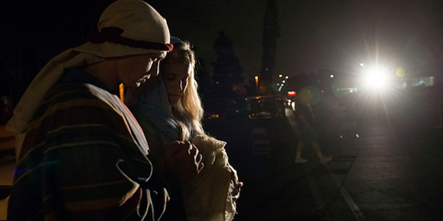 FOUNTAIN VALLEY, CA - DECEMBER 10: Church members Matt and Christi Pobst carry their baby Taylor as they walk to the manger as Joseph and Mary outside the Church of Jesus Christ in Fountain Valley as part of the church's living creche this year. (Photo by Kevin Sullivan/Digital First Media/Orange County Register via Getty Images)