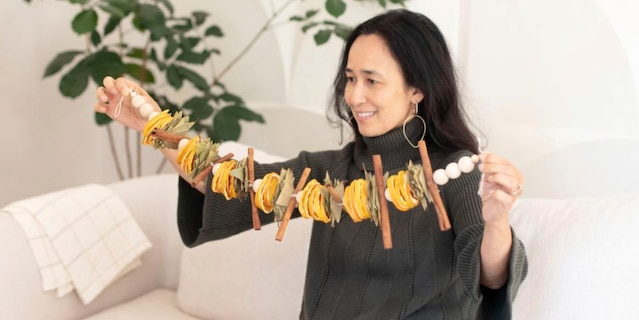 San Francisco Bay-area based Mariam Naficy, shown here, founder of online design marketplace Minted, has been making garlands this year out of various materials, including fragrant dried orange slices. (Minted via AP)