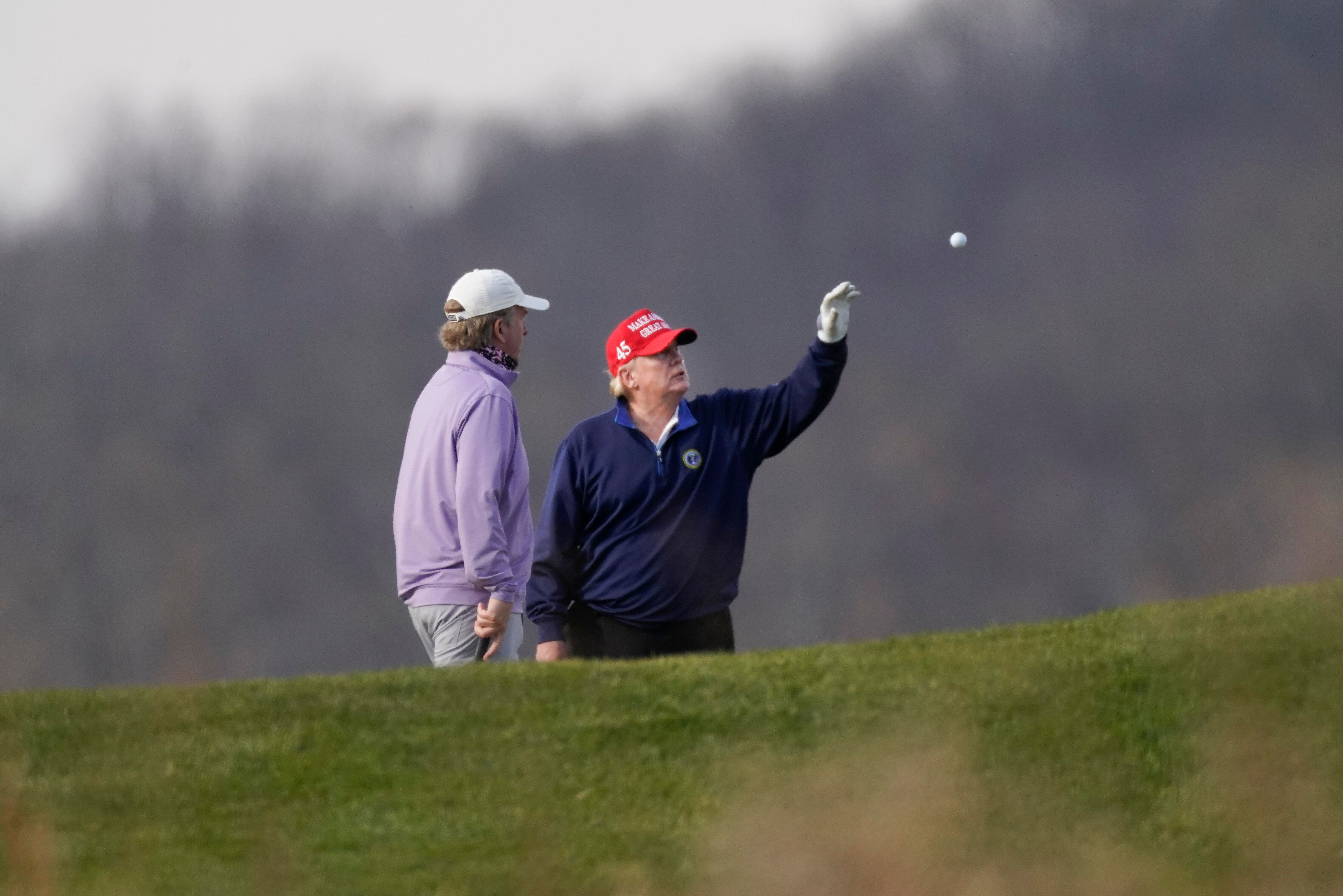 President Donald Trump is tossed a golf ball as he golfs at Trump National Golf Club in Sterling, Va., Sunday, Dec. 13, 2020.