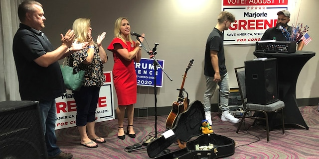 Construction executive Marjorie Taylor Greene, third from left, claps with her supporters at a watch party event, late Tuesday, Aug. 11, 2020, in Rome, Ga. Greene won the GOP nomination for northwest Georgia's 14th Congressional District. (AP Photo/Mike Stewart)
