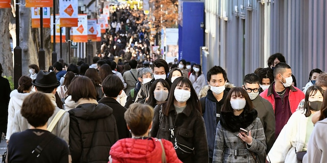 People wearing face masks to help curb the spread of the coronavirus walk on Aoyama shopping street in Tokyo Sunday, Dec. 27, 2020. Japan is barring entry of all nonresident foreign nationals as a precaution against a new and potentially more contagious coronavirus variant that has spread across Britain. The Foreign Ministry says the entry ban will start Monday and last through Jan. 31. (Yuka Ando/Kyodo News via AP)