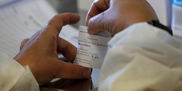 A nurse prepares a dose of the Pfizer-BioNTech COVID-19 vaccine at the Santa Maria hospital in Lisbon, Sunday, Dec. 27, 2020. Portugal started its vaccination program on Sunday with medical personnel in reference hospitals across the country receiving the first shots. (AP Photo/Armando Franca)