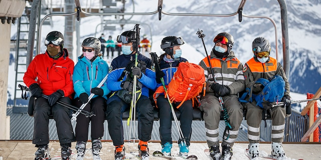 """A policewoman and policeman (center) ride a ski lift as they patrol on the slopes and in alpine restaurants specifically, to check the application of sanitary measures during the coronavirus disease (COVID-19) outbreak, in the alpine resort of Villars-sur-Ollon, Switzerland, Saturday, December 19, 2020. The police receives local support of the """"protection civile"""", civil protection (right), in alpine resort. (Valentin Flauraud/Keystone via AP)"""