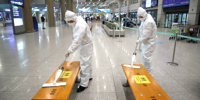 Workers wearing protective gears disinfect chairs as a precaution against the coronavirus at the arrival hall of the Incheon International Airport in Incheon, South Korea, Monday, Dec. 28, 2020. South Korea has confirmed its first cases of a more contagious variant of COVID-19 that was first identified in the United Kingdom. (Kim Sun-woong/Newsis via AP)
