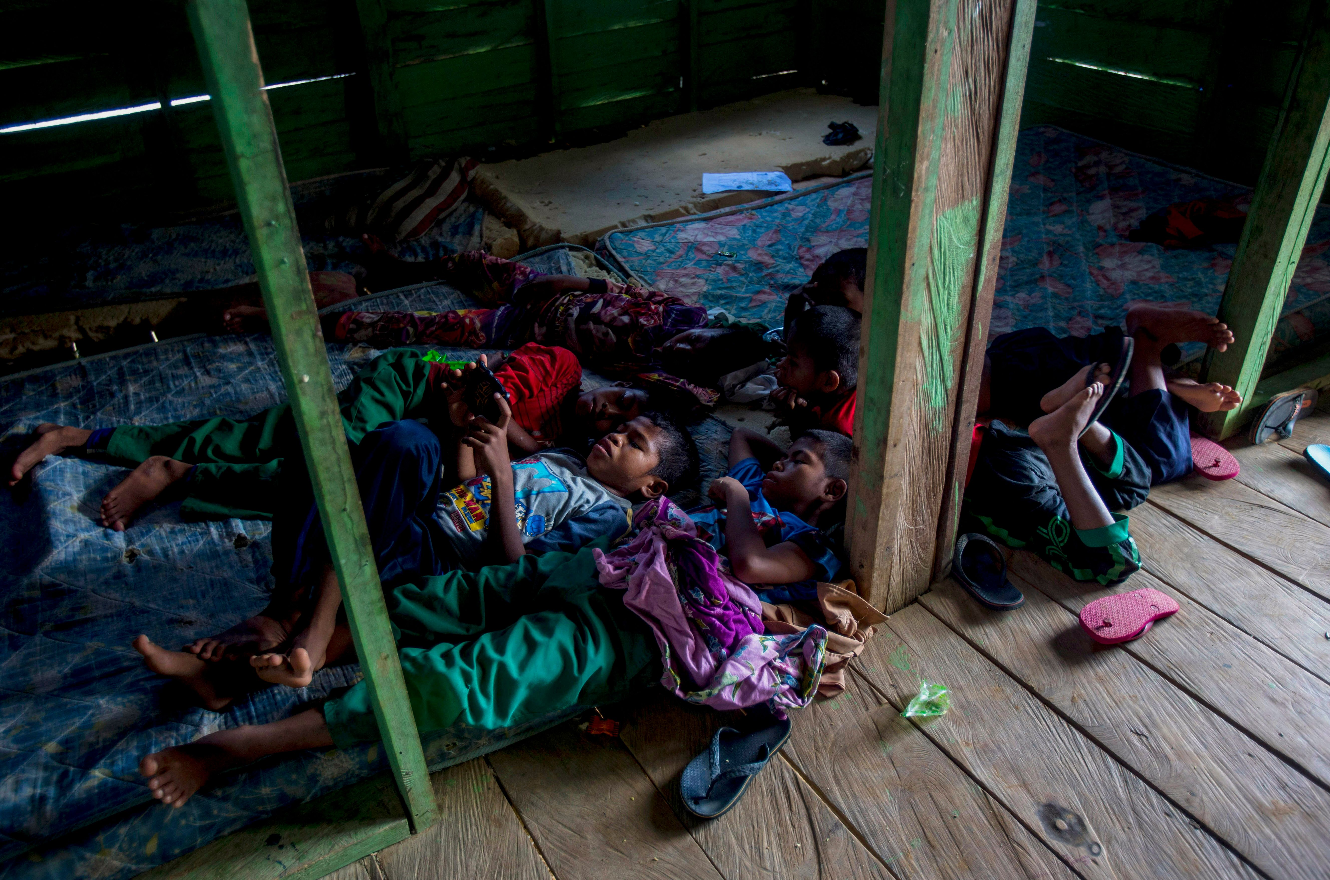 Students of a boarding school rest in their dormitory in North Kalimantan, Indonesia. Some palm oil workers who work illegall