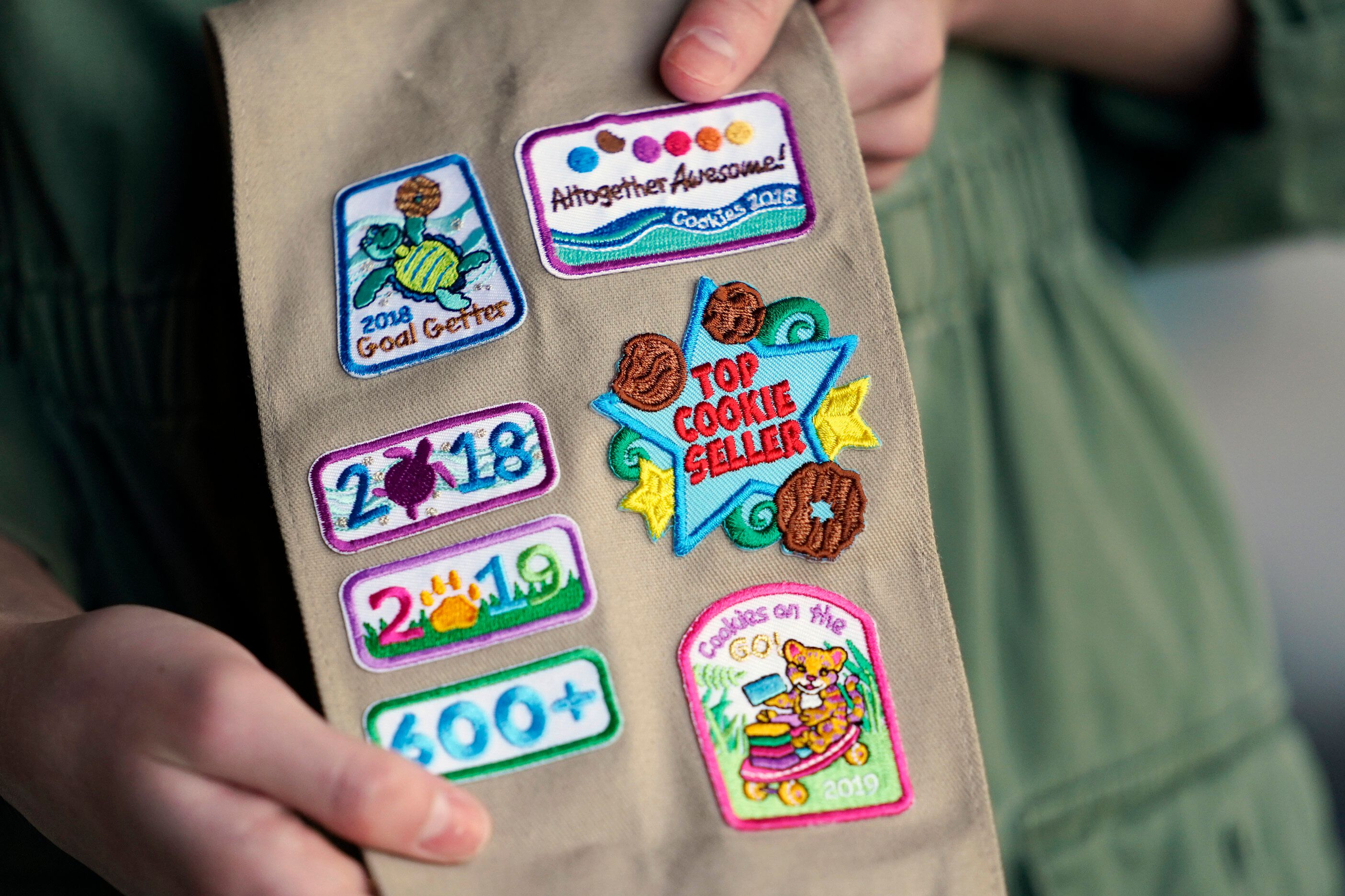 Olivia Chaffin displays merit badges that she has been awarded for selling Girl Scout Cookies in Jonesborough. She was a top