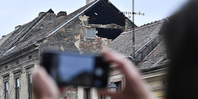A resident takes a photograph of the damage caused by an earthquake in Sisak, Croatia, Monday, Dec. 28, 2020. A moderate earthquake has hit central Croatia near its capital of Zagreb, triggering panic and some damage south of the city. There were no immediate reports of injuries. (AP Photo)