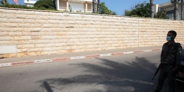 In this September 2020 file photo, an Israeli border police officer stands guard next to the U.S. ambassador's official residence in a suburb of Tel Aviv. An official record shows that the United States sold the ambassador's residence in Israel for more than $67 million in July. (AP Photo/Sebastian Scheiner, File)