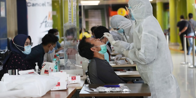 Health workers take nasal swab samples of train passengers to be tested for the coronavirus -- a procedure required for long-distance train trips -- at Gambir Train Station in Jakarta, Indonesia, Tuesday, Dec. 22, 2020. Indonesia has reported more than 600,000 cases of the coronavirus. (AP Photo/Tatan Syuflana)