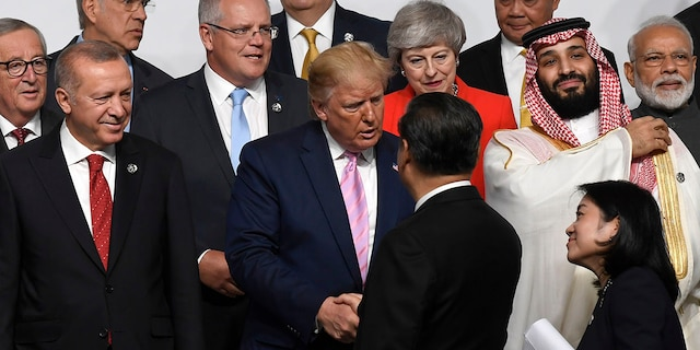 President Donald Trump, center, shakes hands with Chinese President Xi Jinping as they gather for a group photo at the G-20 summit in Osaka, Japan, Friday, June 28, 2019. (AP Photo/Susan Walsh)