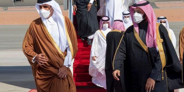 Saudi Arabia's Crown Prince Mohammed bin Salman, right, welcomes Qatar's Emir Sheikh Tamim bin Hamad al-Thani upon his arrival to attend the Gulf Cooperation Council's 41st Summit in Al-Ula, Saudi Arabia, Tuesday, Jan. 5, 2021. (Saudi Royal Court via AP)