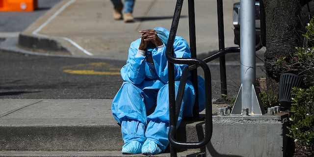 A sad and tired healthcare worker is seen by the Brooklyn Hospital Center in New York, United States on April 1, 2020. (Photo by Tayfun Coskun/Anadolu Agency via Getty Images)